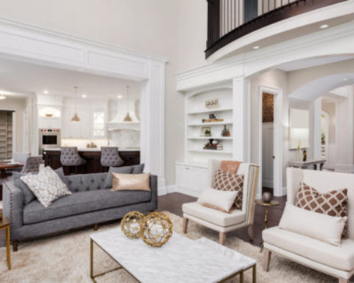 Beautiful living room interior with tall vaulted ceiling, loft area, hardwood floors and fireplace in new luxury home. Has view of kitchen and dining area, and loft.